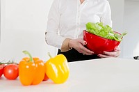 Woman holding bowl of lettuce in kitchen