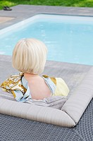 Senior woman sitting on couch by the poolside