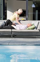 Senior couple by the poolside with man sleeping on couch