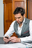 Man at table looking at cell phone