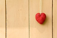 Red heart hanging at wooden wall