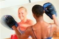 Two women boxing at gymnasium