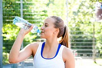 Teenage girl drinking from water bottle