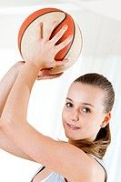 Smiling teenage girl holding basketball