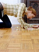 Young woman setting up row of dominoes