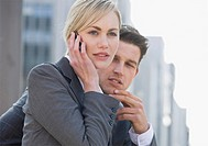 Businessman and businesswoman on cell phone outdoors