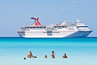 Cruise ship passengers play in water while ship is moored at Half Moon Cay, Bahamas