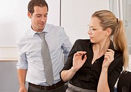 Businessman harassing young woman in office
