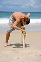 Young man playing cricket on the beach