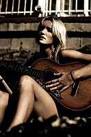 Young blond woman playing guitar outdoors