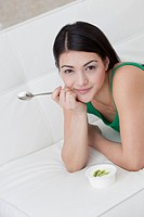 Dark_haired young woman eating yogurt with kiwi