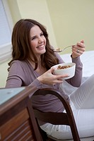 Happy young woman holding bowl of cereals