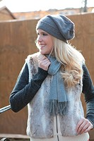 Smiling young woman in winter clothing outdoors