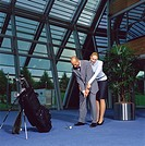 Businessman and Businesswoman Playing Golf in Office