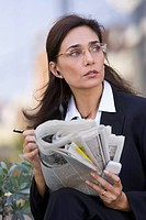 Businesswoman Outside with Newspaper and Phone