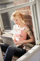 Blond Woman using Laptop on Fire Escape