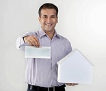 Man holding a house model and cheque