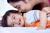 Mother and son smiling on a bed
