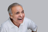 Elderly man laughing over colored background
