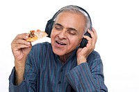 Close_up of senior man eating pizza while listening to music on headphones