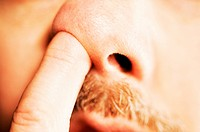 Extreme close_up of man's finger in his nose