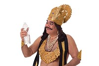 Man dressed as Raavan looking at a bottle of water