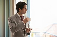 Smart young businessman having cup of tea while thinking