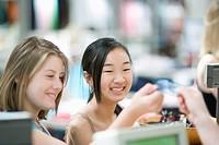 Teenage Girl Giving Credit Card to Clerk