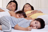 Portrait of boy holding chocolate while his family sleeping in the background