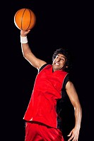 Basketball player in air preparing to dunk ball over black background
