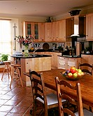 Apples are kept in the fruit bowl and a flower vase is seen on the counter of an exquisite kitchen