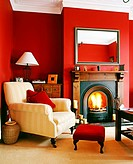 An armchair and candles are seen near the fireplace in a red living room