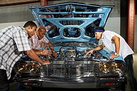 Young Men Repairing Motor in Customized Car