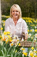 Portrait of smiling woman with basket picking spring flowers in sunny garden