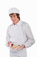 Cut Out Of Trainee Chef Holding Dessert Facing Camera