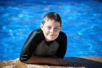 young male smiling at the camera from a swimming pool