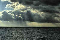 Japan, Sun shining through dramatic clouds over sea
