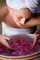 Woman Washing Face in Rose Petal Water