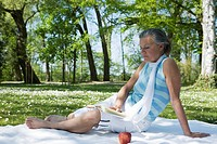 Woman Reading on Picnic Blanket