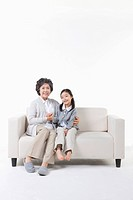 A grandmother and granddaughter on the couch