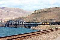 Freight Train crossing the Columbia River heading toward Portland, Oregon with the Cascade Range in distance, USA