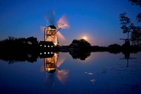 Netherlands, Kinderdijk, Illuminated windmill at moonrise
