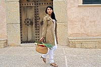 Young Woman Carrying Produce in Basket