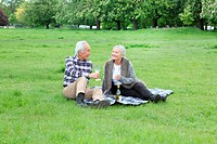 Older couple having wine at picnic