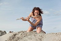 Young woman with flute on the beach