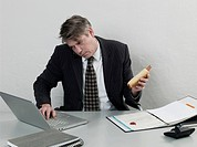 Businessman Dripping Ketchup from Hot Dog on Desk