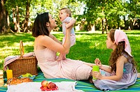 Mother and her two children having picnic in park