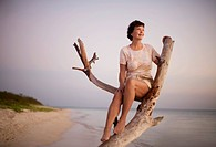 Woman Sitting on Driftwood on Beach