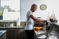 Smiling man in kitchen making fresh orange juice