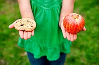 A girl holding a cookie and an apple